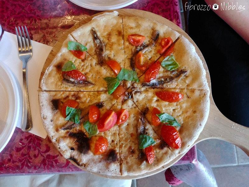 Pizza di solina con pomodorini, acciughe e basilico